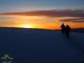 Wędrowcy na RAKIETACH ŚNIEŻNYCH podążający w stronę zachodzącego słońca nad Bieszczadami.