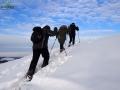 Grupa wspinająca się na rakietach śnieżnych na połoniny w głębokim śniegu.