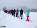 Grupa wędrująca na rakietach śnieżnych po widokowych wzgórzach nad Lutowiskami.