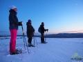Wędrowcy na rakietach śnieżnych wpatrzeni w zachód słońca.