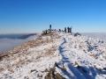 Nieliczni turyści (sami przewodnicy!) wpatrzeni na szczyty wystające z mgieł dzięki inwersji.