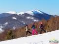 Wędrowcy na rakietach śnieżnych z widokami na Połoninę Wetlińską.