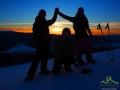 Wędrowcy na rakietach śnieżnych o zachodzie słońca na zboczach Połoniny Caryńskiej.