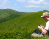 Turysta przeglądający wykonane zdjęcia ze zboczy Pikuja w stronę Starostyny.