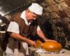 Piekarz rozcinający chleby z gorącymi wewnątrz golonkami. Takie atrakcje organizujemy do degustacji win podczas wycieczek jednodniowych na Węgrzech...