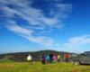 Turyści wpatrzeni na widoki ze szczytu góry i wsłuchani w opowieści przewodnika podczas wyprawy UAZ-ami na pograniczu Bieszczad i Beskidu Niskiego.