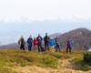 Grupa przewodników i pracowników Biura Podróży Bieszczader na zboczach góry Pikuj, a z widokiem na pasmo Borżawa.