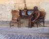 Pomnik Ignacego Łukasiewicza siedzącego przy restauracji Lampa Naftowa w centrum Lwowa, do której wnętrza wchodzimy na wycieczkach jednodniowych z Bieszczad zimą.
