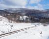 Przysypane śniegiem tory bieszczadzkiej ciuchci i widok na pasmo górskie Wysoki Dział. Zdjęcie wykonane przy Bieszczadzkiej Obwodnicy Karpackiej.