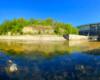 Zdjęcie panoramiczne od zapory wodnej tworzącej Jezioro Sieniawskie po koryto rzeki Wisłok wraz z umocnieniami betonowymi brzegów rzeki.