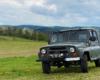 Samochód terenowy UAZ na pograniczu Bieszczad i Beskidu Niskiego wczesną wiosną otoczony górami i kwitnącymi drzewami...