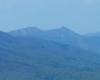 Zdjęcie jednego zbocza Połoniny Caryńskiej, a przede wszystkim widok na Połoninę Wetlińską, podziwianą z pochmurny dzień z wycieczki pieszej po Bieszczadzkim Parku Narodowym na Bukowe Berdo.