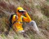Wędrowca schowany pośród traw połonin podczas wędrówki po Bieszczadzkim Parku Narodowym - silny wiatr na Bukowym Berdzie.