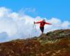 Turystka próbująca złapać równowagę na silnym wietrze wiejącym na Bukowym Berdzie w Bieszczadzkim Parku Narodowym - to był świetny pomysł na wycieczkę jednodniową po regionie Bieszczad.