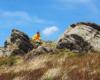 Wędrowiec schowany między skałami na szlaku prowadzącym po Bukowym Berdzie schowany między skałami przed podmuchami silnego wiatru podczas słonecznej pogody. Najbardziej polecamy wycieczki wiosną i jesienią po Bieszczadzkim Parku Narodowym.