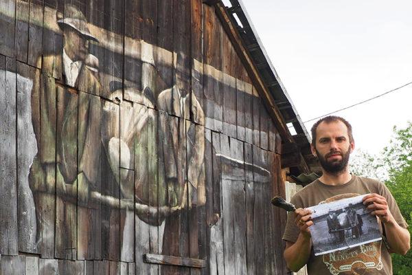 Artysta Arkadiusz Andrejkow przed muralem ' deskalem na granicy Łukawicy i Bezmiechowej w Bieszczadach z pracą dotyczącą szybowców.