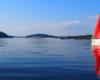Żaglówka płynąca po Zalewie Solińskim w tle zaporą wodną w Solinie - tędy płyniemy statkiem na wycieczce jednodniowej Bieszczady w pigułce, którą nazwaliśmy również śladami serialu kryminalnego Wataha.