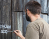 Artysta Arkadiusz Andrejkow przed muralem / deskalem swojego autorstwa na granicy Bezmiechowej i Łukawicy przedstawiający szybowiec i ludzi go niosących z 1931 roku - to niezwykły człowiek tworzący niepowtarzalne atrakcje w Bieszczadach i pomagający zachować historie zwykłych ludzi...