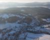 Widok na Komańczę oraz łąki i lasy nad miejscowością Czystogarb podczas lotu paralotnią nad Bieszczadami.