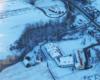 Szkoła i drewniana cerkiew prawosławna w Komańczy widziane z paralotni zimą.